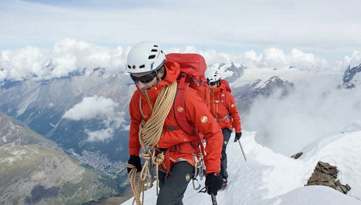 A man climbing the mountains wearing a hardshell jacket to keep his warm