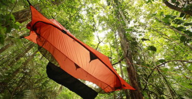 Orange tent hammock hanging in the forest
