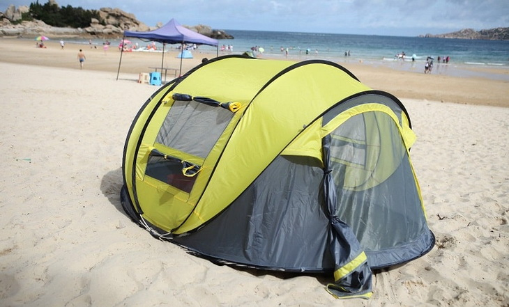 A four person tent on a beach in summer time