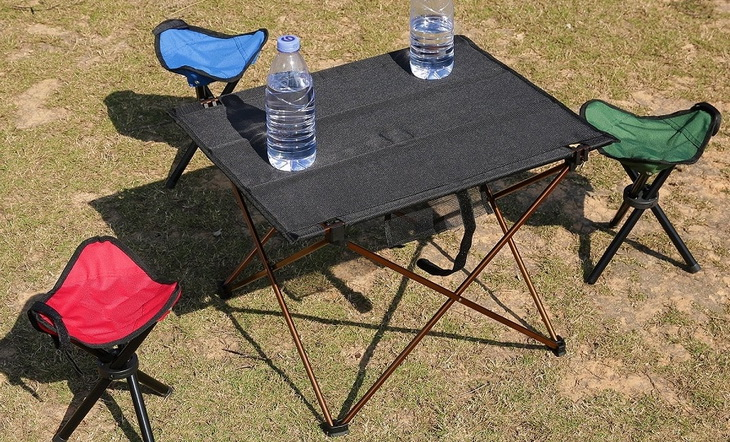 Camping-folding-table with two water bottles on it