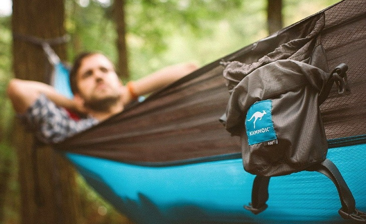 Image of a man relaxing in a hammock in a forest