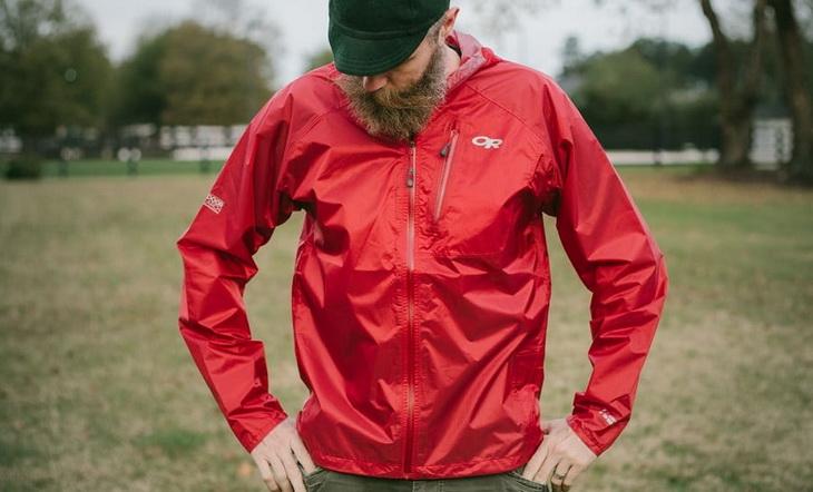 A man looking at his rain jacket