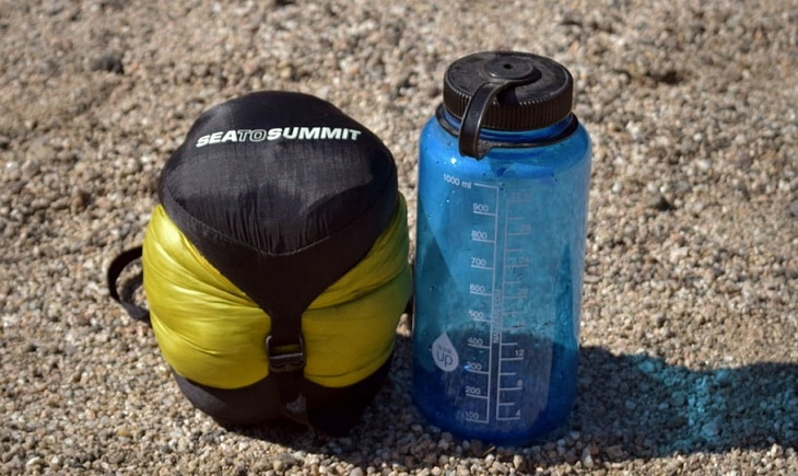 Sleeping bag next to a water bottle