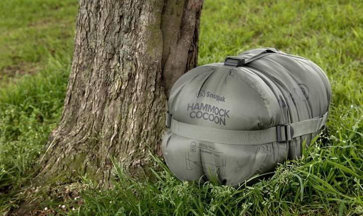 Compression-sack-for-a-sleeping-bag near a tree