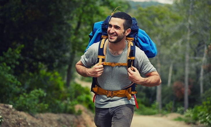Happy hiker on a mountain road