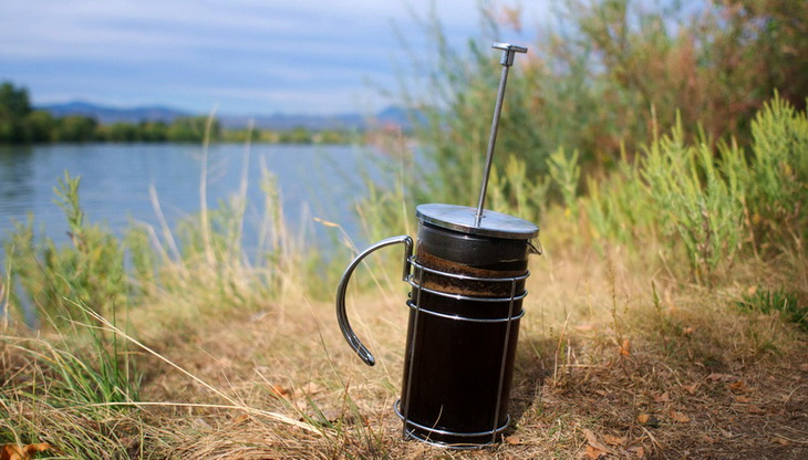 French Press Coffee Maker on the grass near a water