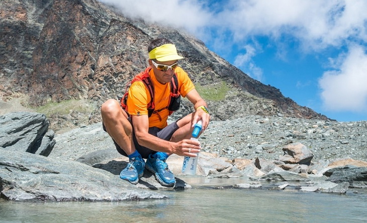 A hiker using a water filtration system