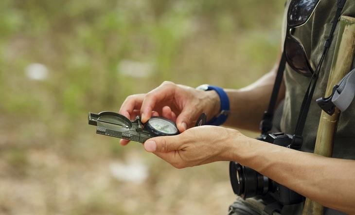 Hands of tourism holding compass: orientation concept