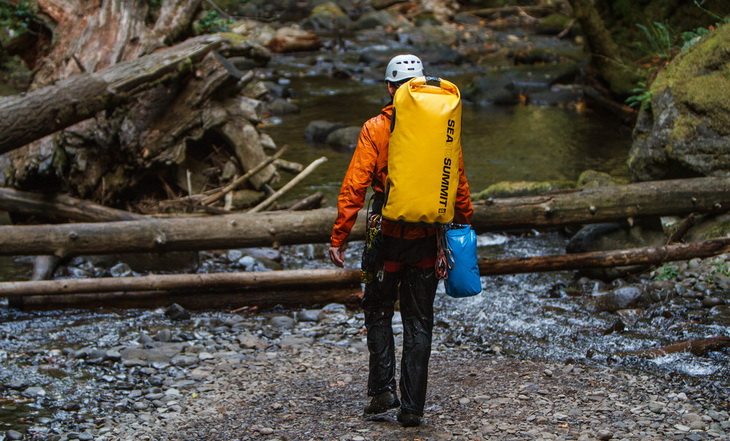 A man carrying Sea to Summit Hydraulic Dry Pack (65L)