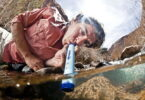 A man drinking water from the LifeStraw Water Purifier wich is the Lightest Backpacking Water Filter