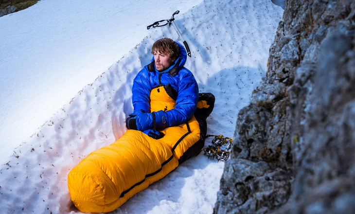 A man getting rest on top of the mountain in a sleeping bag