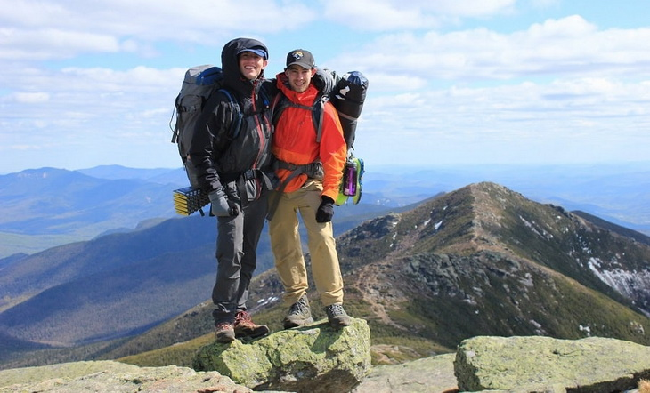 Two hikers smiling on top of the mountains