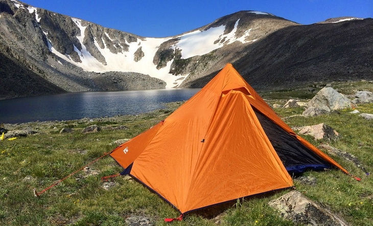 Image of a solo tent on top of the mountains near a lake
