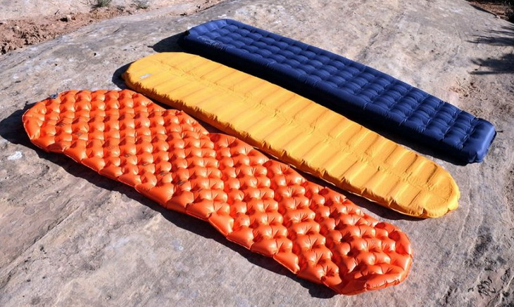 Types of sleeping pads on the ground outside in the sun