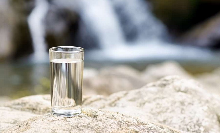 A glass of water on rocks near a waterfall