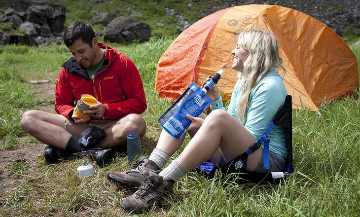A woman drinking water from a backpacking filter