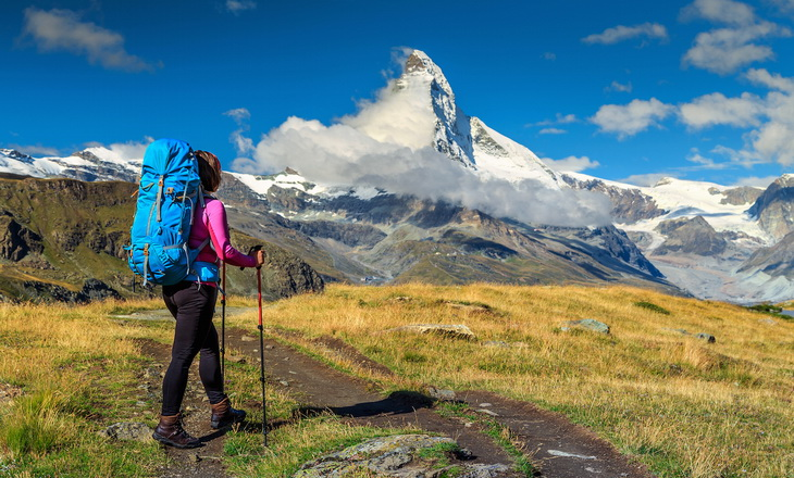 Hiker woman with backpack and mountain equipment,looking at view in Valais region,Matterhorn,Switzerland,Europe