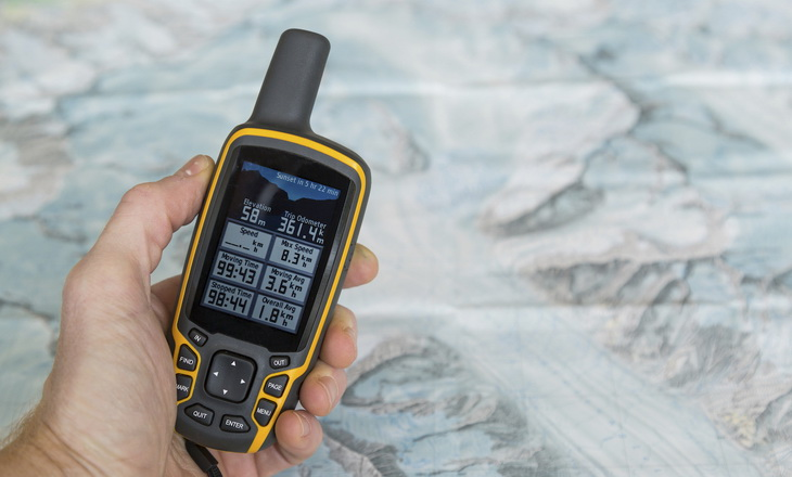 A man is helding an outdoor GPS and a hiking map of a mountain range.