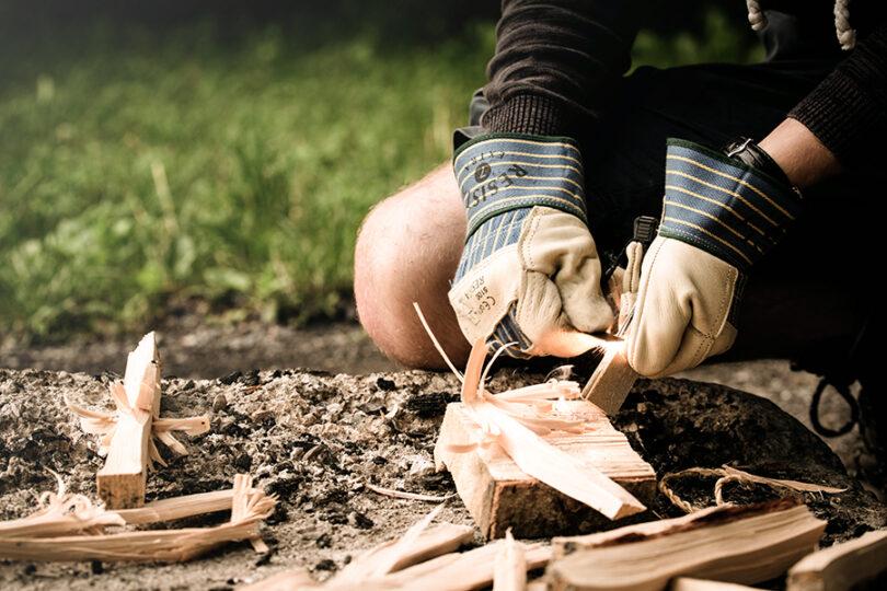 man wearing gloves starting a fire