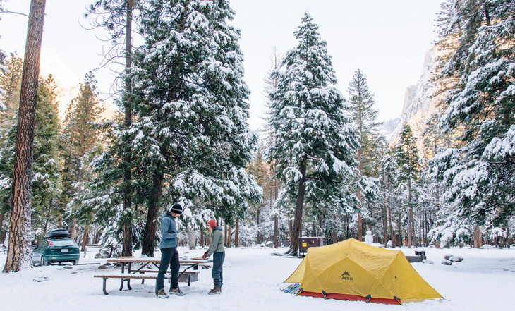 Two adults in the forest next to a 4-Season Camping Tent