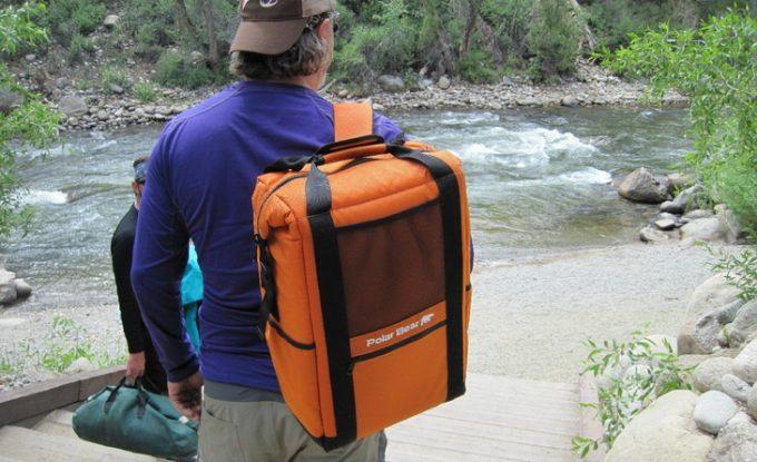 A man wearing a cooler backpack on his shoulder