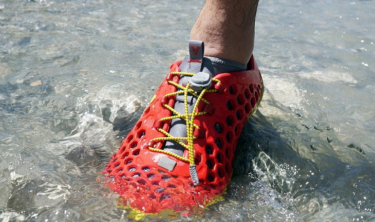 A man stepping into water wearing a pair of water shoes