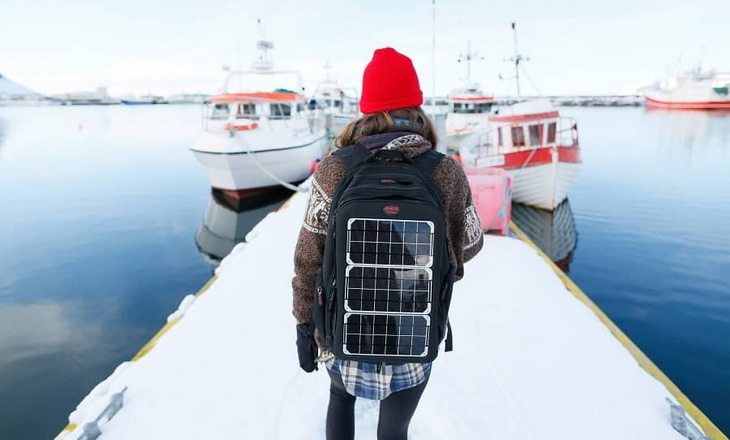 A woman with a solar backpack sitting in a port