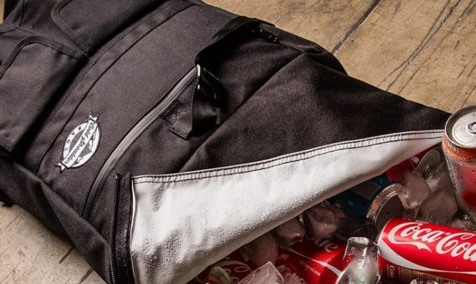 A cooler bag full of coca cola on the floor