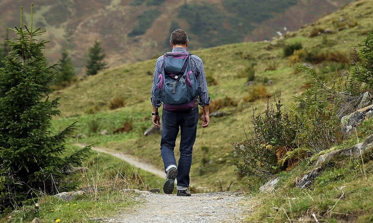 A man with a backpack hiking the mountains