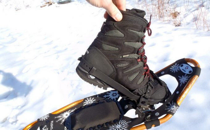 A person holding a pair of snowshoeing boots