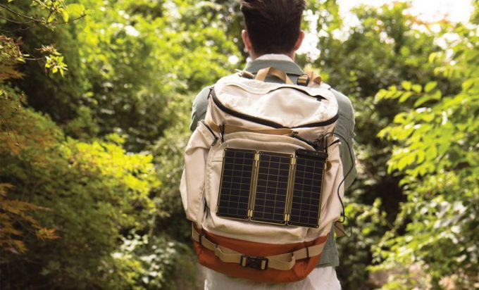 A man with a portable solar charger on his backpack
