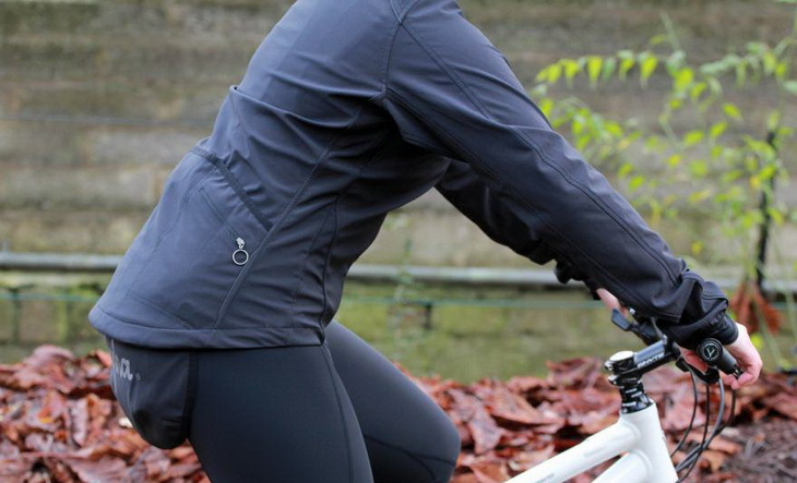 A womna on a bike wearing Rapha softshell jacket