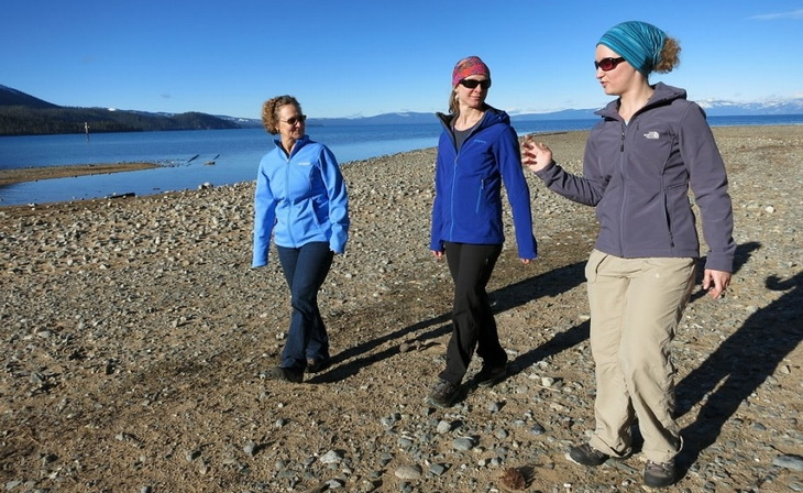 Three womens wearing softshell jackets hiking near a water