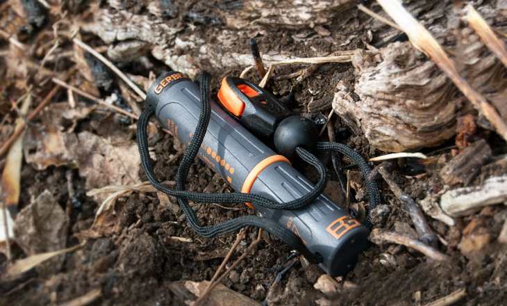 The Bear Grylls Fire Starter on the ground in a forest