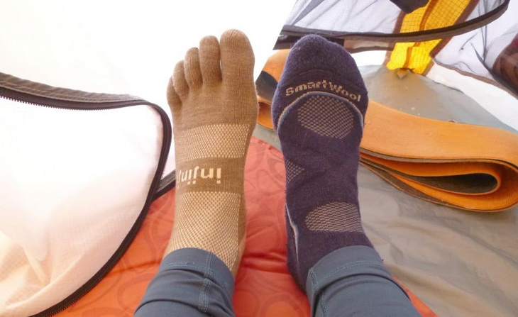 A person is testing two different type of warm socks in a tent