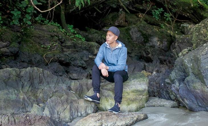 A guy sitting on a rock wearing a windbreaker-jacket