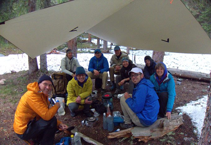 group of hikers under tarp