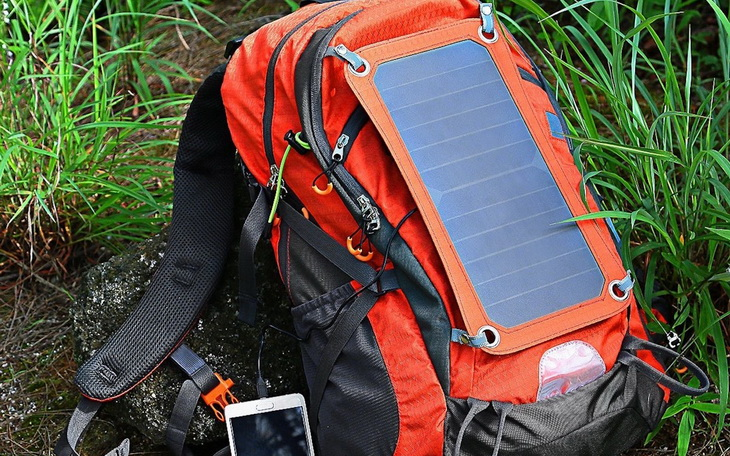 A solar backpack and a smartphone next to him