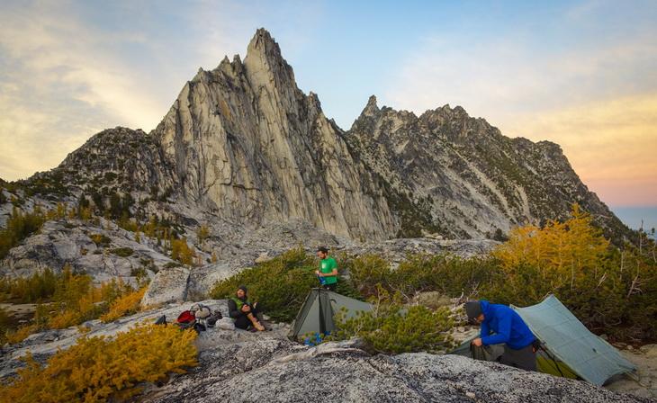 Three mens next to three camp tents