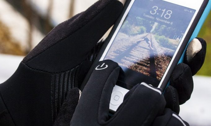 A man weaaring a pair of winter gloves alos used for touchscreen of the smarphone