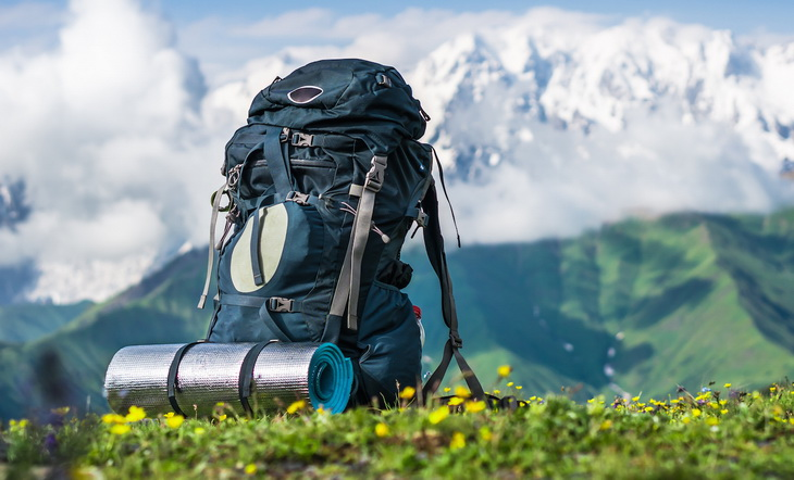 Tourist backpack and sleeping pad on a background of mountains, Georgia (Svaneti)