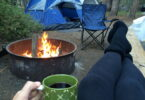 A woman relaxing with a cup of coffee in the camp near a fire and a tent