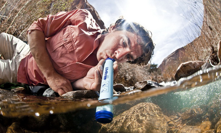 A man drinking water with a Lifestraw Water Filter