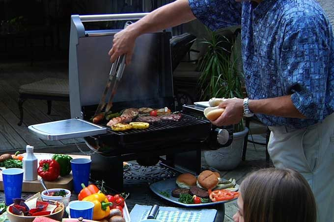 man cooking on portable gas grill
