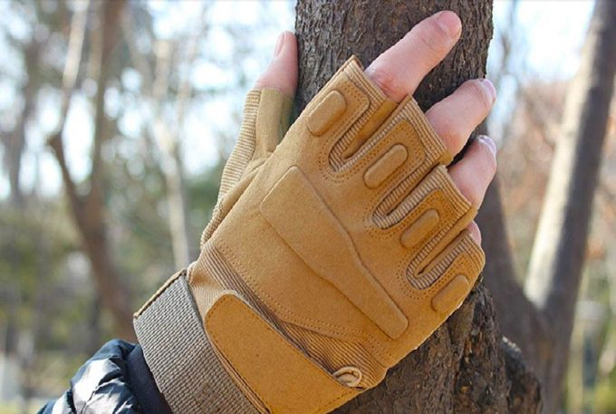man with fingerless glove touching tree