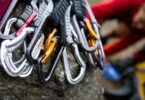 A pile of quick draw carabiners with climbers out of focus in the background.