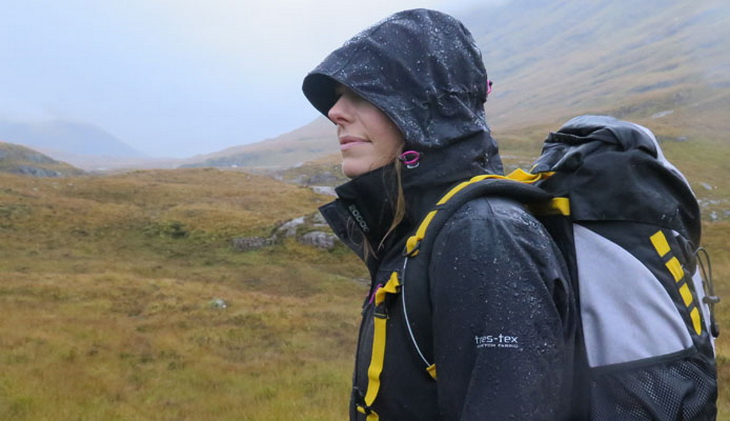 A woman wearing a waterproof jacket is hiking on the mountains