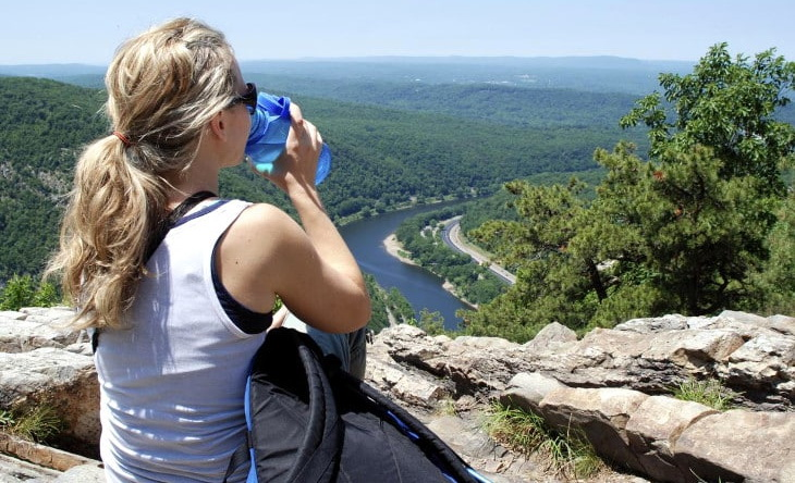 A woman hiker drinking water from a water bottle