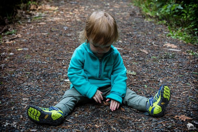 child sitting on ground with hiking shoes