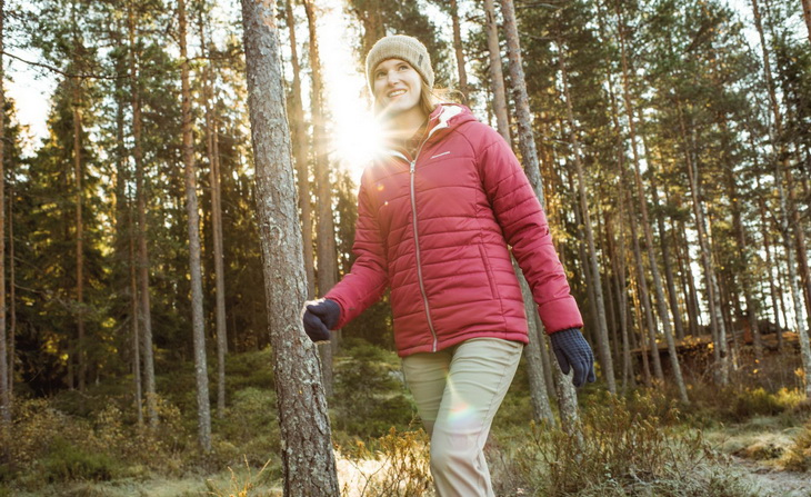 Woman wearing a red parka jacket is hiking in the forest
